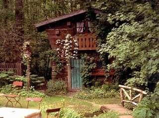 kleine, zweistöckige Holzhütte, teilweise von umstehenden Bäumen verdeckt, davor eine Wiese und ein bestuhlter Tisch