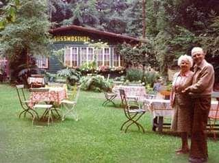 Mosthof im Hintergrund, davor einige bestuhlte Tische, rechts älteres Ehepaar